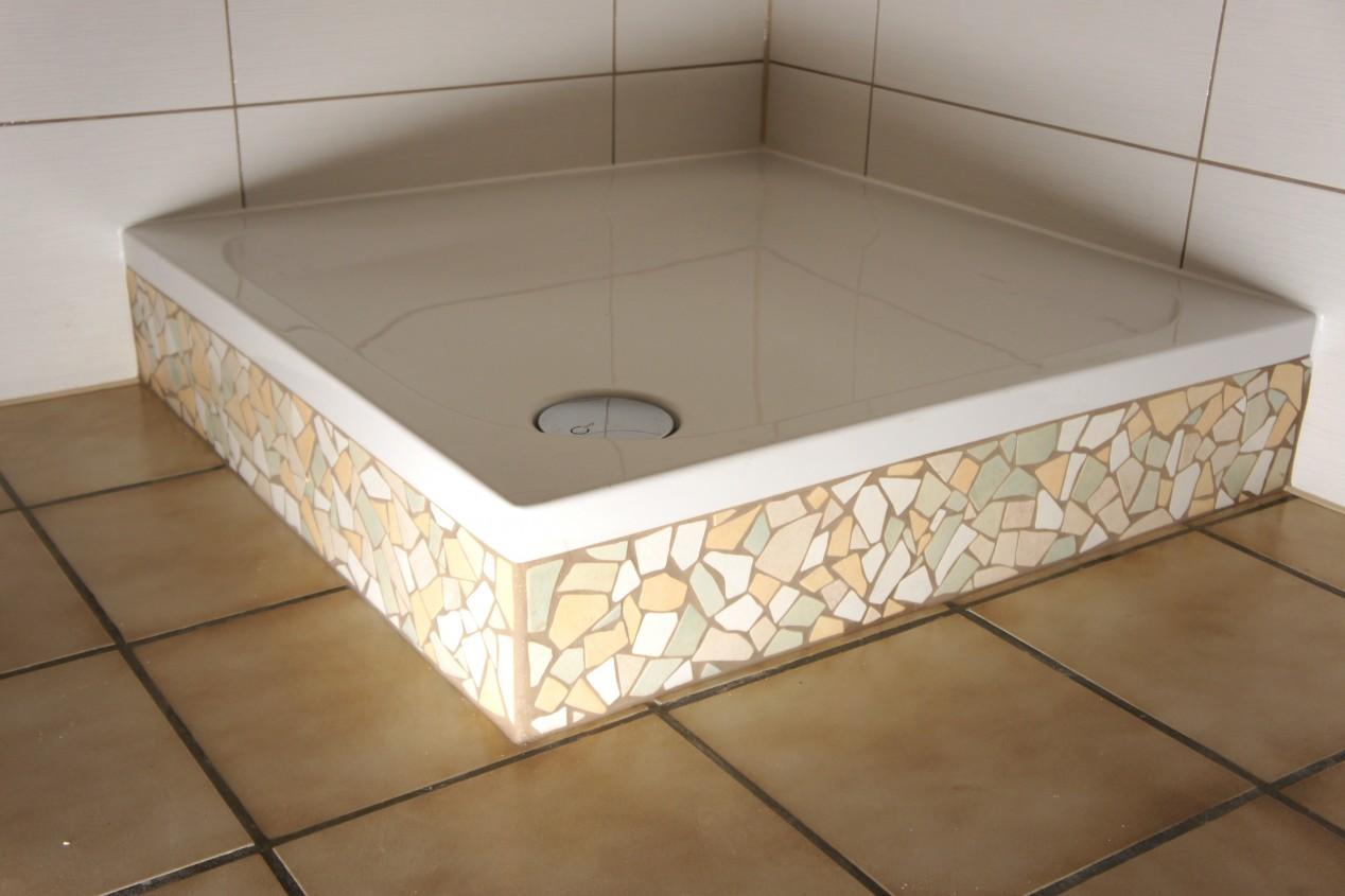 Duschtasse mit Mosaikfliesen in einem gefliesten Badezimmer